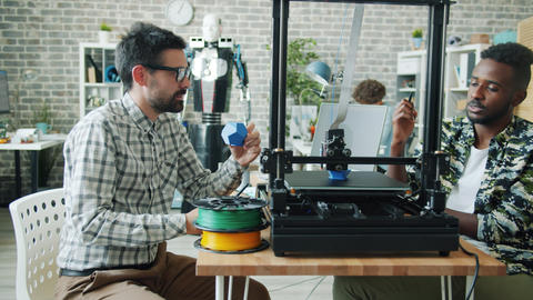 Slow motion of guys discussing 3d printing process in office watching equipment Footage