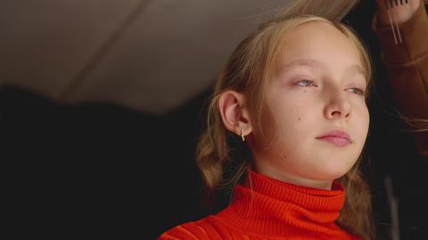 Portrait young girl receiving hair style in dark hairdressing studio. Hair Footage