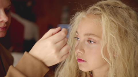 Makeup artist applying makeup eyebrows with cosmetic brush close up. Visagiste Live Action