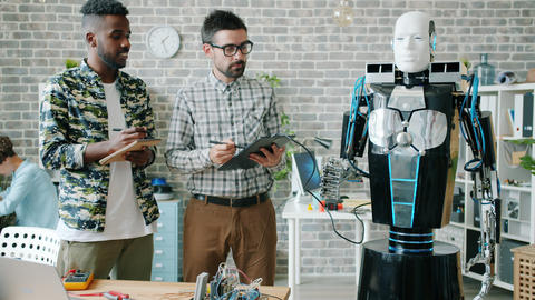 Young men testing robot using tablet in office talking enjoying technology Footage