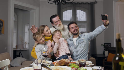 Attractive happy family waving hands while making selfie at the family feast Footage