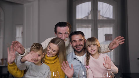 Lovely charming family with nice smiles posing on camera while waving their Archivo