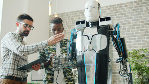 Successful engineers testing cool robot in laboratory using tablet indoors Footage