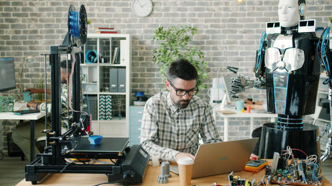 Young male scientist working with robot, laptop and 3d printer in workplace Live Action