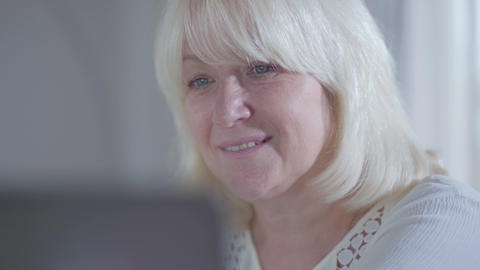 Close-up face of attractive mature Caucasian woman looking at laptop screen and Footage