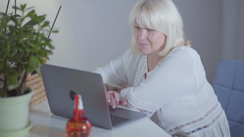 Side view of attractive blond Caucasian mature woman sitting with laptop at home Footage
