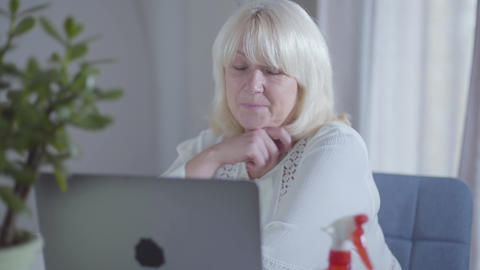 Senior Caucasian woman watching movie on laptop screen and smiling. Happy female Footage