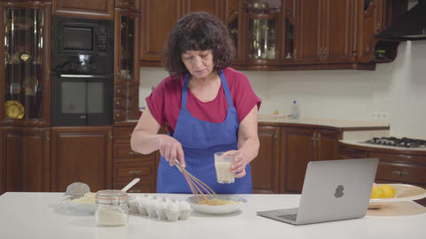 Senior Caucasian woman checking recipe online and mixing milk into dough Footage
