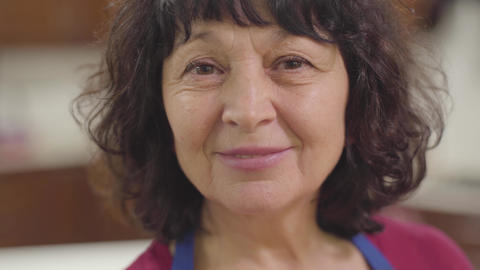 Close-up face of a smiling senior Caucasian woman with brown eyes and curly hair Footage