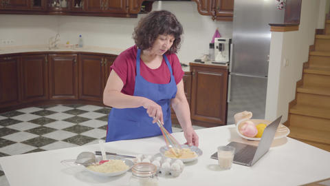 Brunette Caucasian mature woman cooking at the kitchen at home. Senior retiree Footage