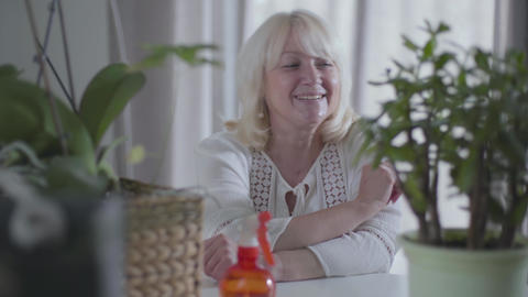 Portrait of happy Caucasian senior woman admiring her houseplants. Nice mature Footage