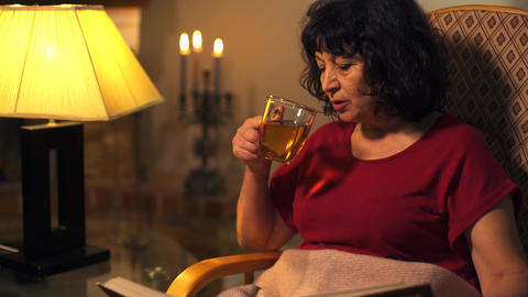 Close-up of mature Caucasian woman drinking tea and looking at photo album. Nice Footage