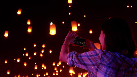 Asian woman watches as sky lanterns fly Into the night sky Footage
