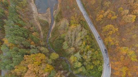 Drone following cars driving on dangerous road in the mountains near lake Live Action