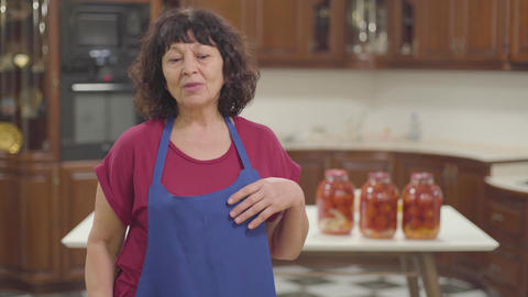 Tired Caucasian retiree taking off blue apron and fixing her curly hair. Senior Footage