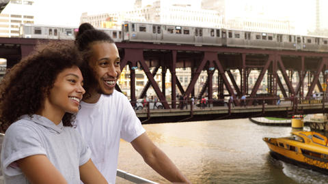 Cute African American couple walk together along the Chicago River GIF