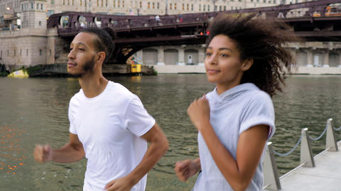 Cute African American couple jogging together along the Chicago River Archivo