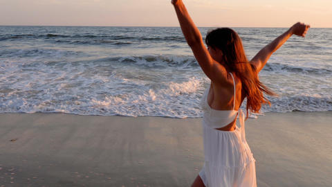 Beautiful woman in a white dress at the beach at sunset GIF
