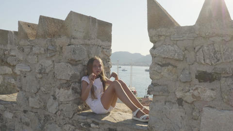 Happy girl sitting and dancing on stone wall GIF