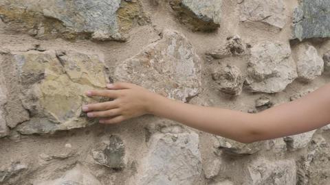 Cropped shot of human hand touching stone wall Archivo