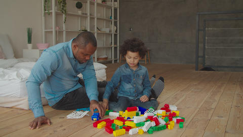 Black father and son plaiyng with building blocks Archivo
