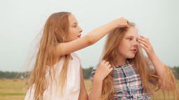 Girl touching hair of female friend outdoor GIF