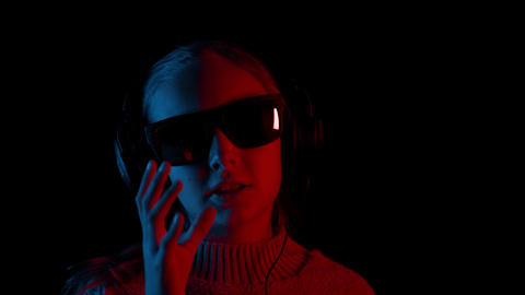 Happy girl in headphones and sunglasses singing in darkness Footage