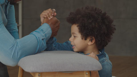 Joyful son defeating father in arm wrestling game Footage