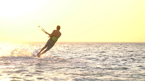 Bright sunshine, sunset and a young man kitesurfing in Dead Sea, Egypt Live Action