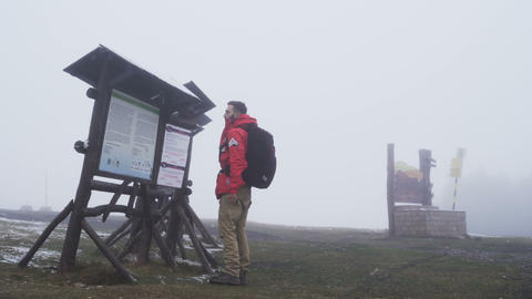 Lost tourist reading map and looking for shelter from the rain Footage