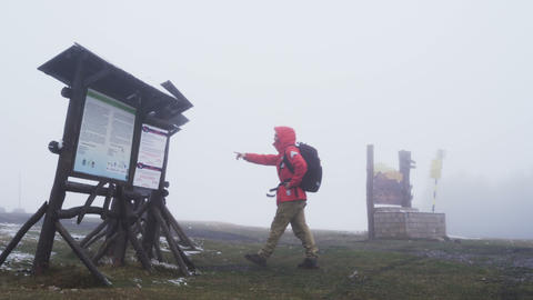 Tourist lost in the fog wearing red jacket reading map on top of the mountain Footage