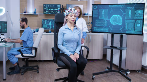 Woman wearing brainwave scanning headset sitting on a chair Footage