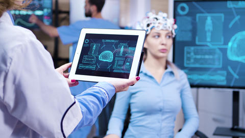 Middle age female doctor holding tablet with patient brain activity Footage
