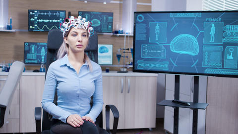 Young female patines sitting on a chiar and wearing brainwaves scanning headset Footage