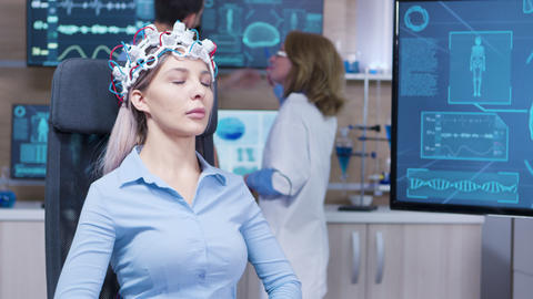 Female patient sitting on a chair and wearing brain activity sensors Footage