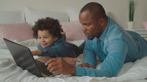 African father and son networking with laptop on bed Archivo