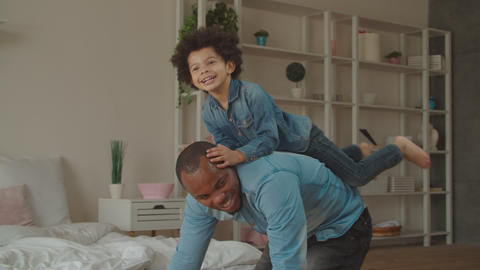 Excited son riding on black father's back at home GIF