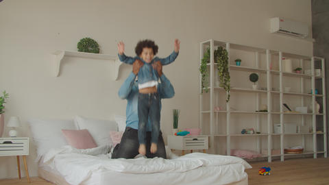 Joyful black father and little son jumping on bed GIF