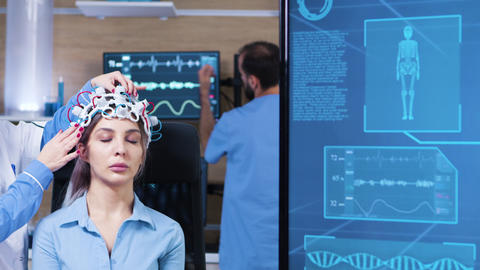 Female doctor in neuro science making adjustments on patient headset Footage
