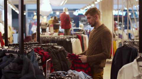 Young man is looking for clothes in a store Footage