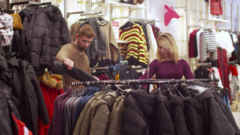 Young woman helps her man to choose a jacket Footage