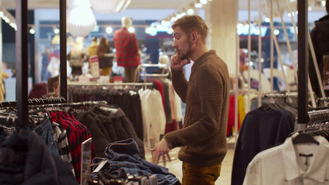 Man chooses clothes and talk on phone Footage
