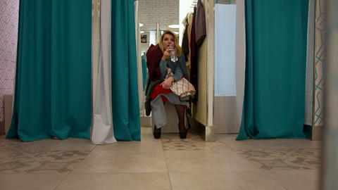 Nice girl sits in the fitting room and is waits for something Footage