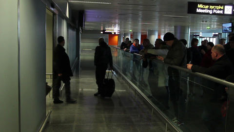 People with bags coming out of airport arrival zone to meeting point Footage