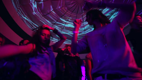 Jib shot from low angle to high angle, people dance in night club during party Live Action