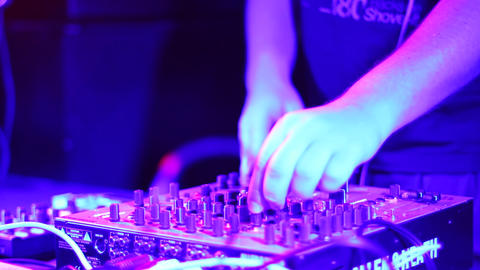 DJ puts on headphones and plays disco set in night club Footage