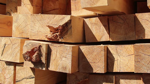 Stack of square wooden chips at construction yard. Dolly pan shot, blue sky Footage