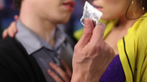 Male offers condom to his female partner. Flirting man and woman. Contraception Footage
