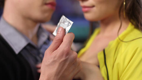 Man offers woman condom she opens it up tearing the envelope. Safe love no risk Footage