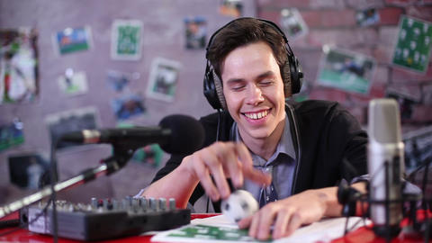Young man smile. Smiling radio DJ or TV show presenter on the air in studio Footage